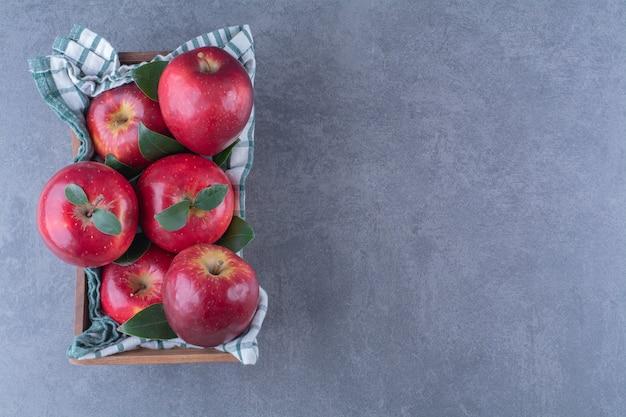 Jabłka z liśćmi na ręczniku na pudełku na marmurowym stole.