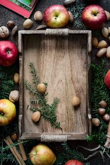 Jabłka z mieszanymi orzechami wokół drewnianej tacy
