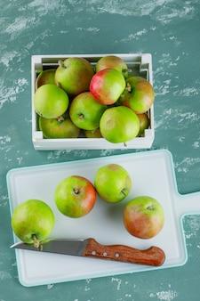Jabłka z nożem w drewnianym pudełku na tle tynku i deski do krojenia, widok z góry.