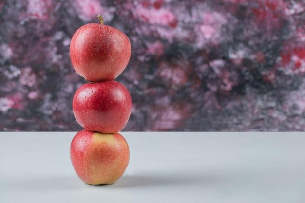 Jabłka z rzędu na białym tle na białym stole.