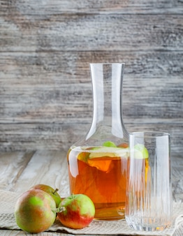 Jabłka z sokiem, szkło na ręczniku drewnianym i kuchennym, widok z boku.