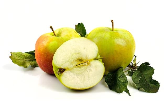 Jabłka z zielonymi listkami z drzewa na białym tle