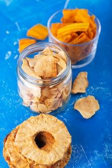 Jabłko, ananas i chipsy z mango w słoiku i kawałki tych owoców na stole