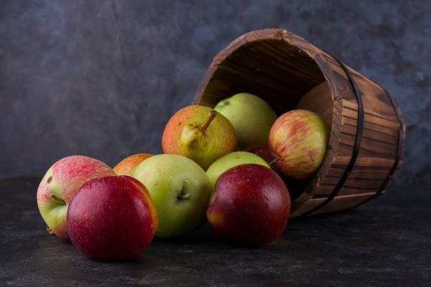 Jabłko, brzoskwinia i gruszki z drewnianego wiadra