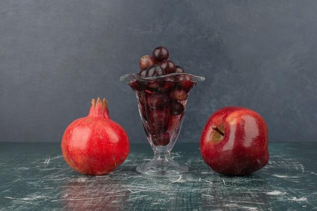 Jabłko, granat i kieliszek czarnych winogron na marmurowym stole