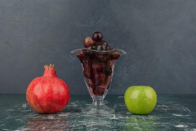 Jabłko, granat i kieliszek czarnych winogron na marmurowym stole.