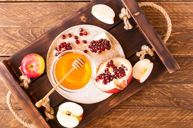 Jabłko, granat i miód na drewnianej tacy widok z góry. tradycyjna żywność żydowskiego nowego roku - rosz haszana.
