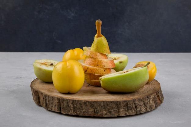 Jabłko, gruszka i brzoskwinie na kawałku drewna na niebieskim tle