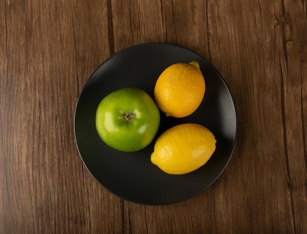 Jabłko i dwie cytryny na ciemnym talerzu. widok z góry