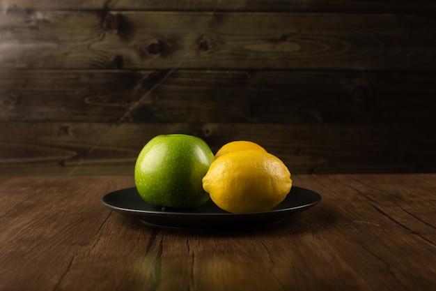 Jabłko i dwie cytryny na ciemnym talerzu.