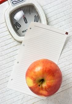 Jabłko i notatka na wadze podłogowej