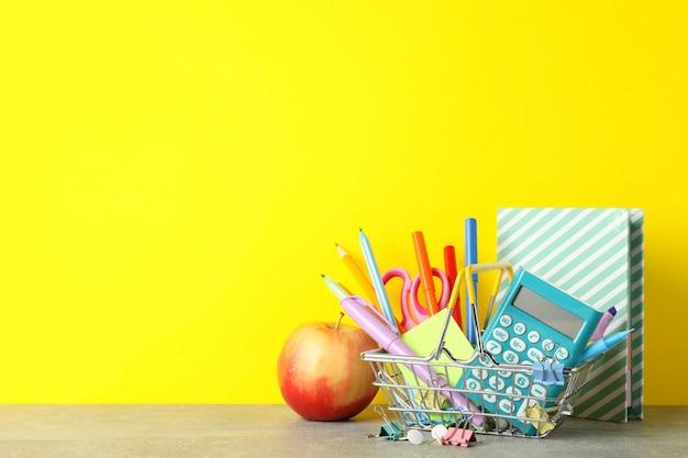 Jabłko i stacjonarne na szarym stole. koncepcja nauki