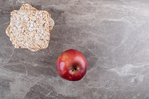 Jabłko i stos dmuchanych wafli ryżowych na marmurowej powierzchni