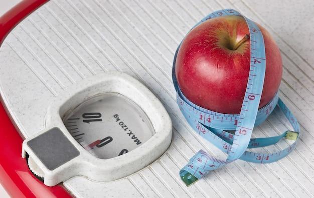 Jabłko i taśma pomiarowa na skale podłogi na białym tle