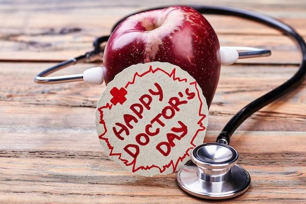Jabłko, karta na dzień lekarza, stetoskop. medyczne święto narodowe.