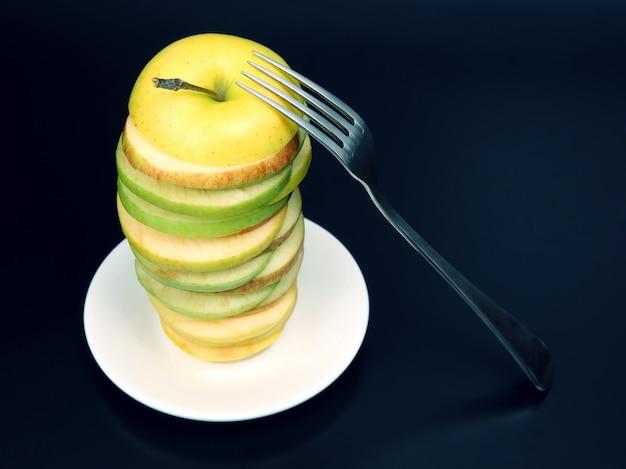 Jabłko pokroić widelcem na kawałki na białym spodku