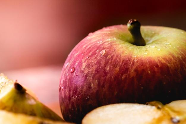 Jabłko w makrofotografii z kilkoma kroplami wody z kawałkami jabłka w kompozycji in