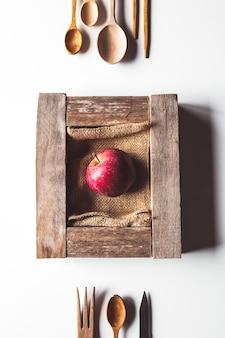 Jabłko w starym drewnianym pudełku ze sztućcami. koncepcja zrównoważonego stylu życia.