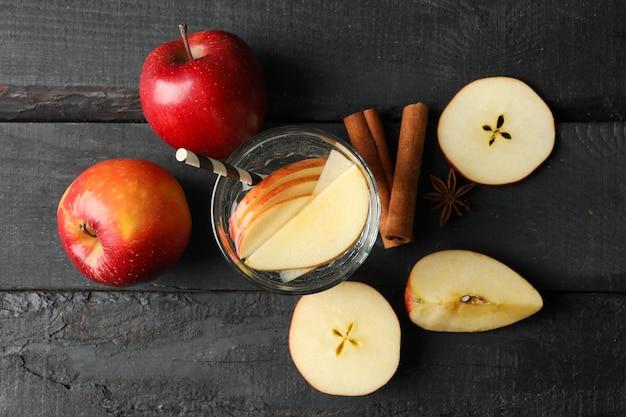 Jabłko, woda i cynamon na drewnie, odgórny widok