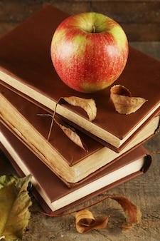 Jabłko z książkami i suchymi liśćmi na drewnianym