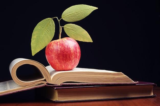 Jabłko z liśćmi i otwartą książką na stole