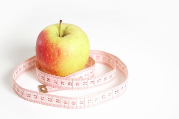 Jabłko z miarą taśmy, diety, koncepcji opieki zdrowotnej i ciała