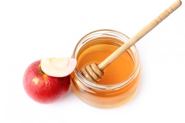 Jabłko z miodem odizolowywającym na białym tle