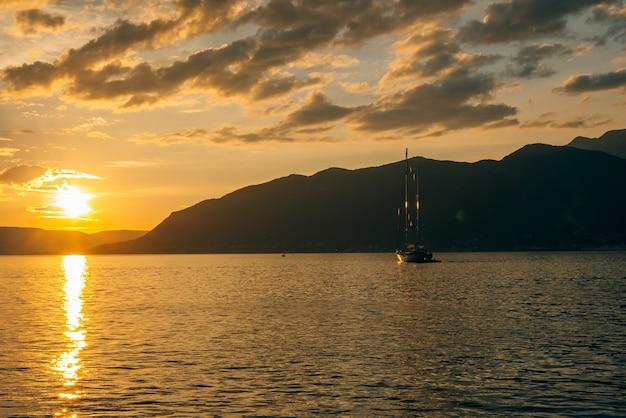Jacht na morzu o zachodzie słońca sylwetka jachtu