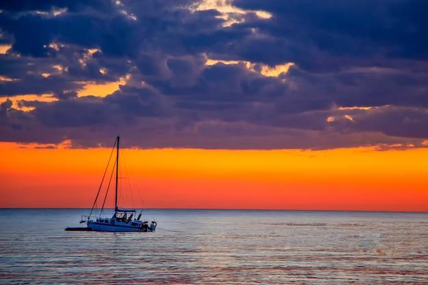 Jacht na morzu o zachodzie słońca