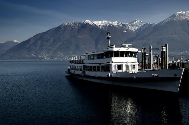 Jacht na morzu otoczony wzgórzami pokrytymi zielenią i śniegiem w słońcu
