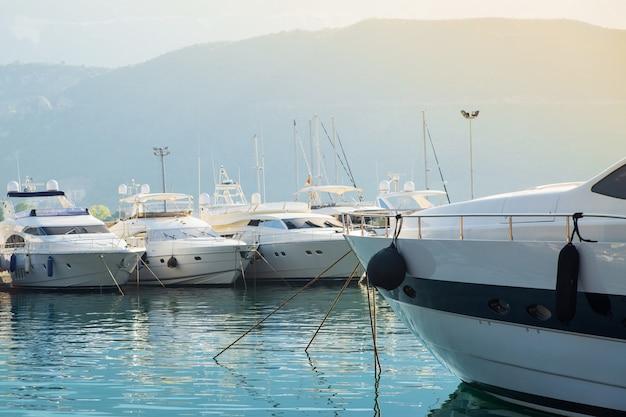 Jacht na tle portu łodzi i góry w słońcu