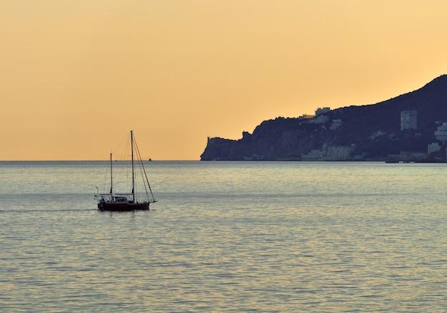 Jacht na wodach morza czarnego u wybrzeży jałty niebo to złoty morski minimalizm