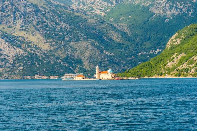 Jacht płynie w pobliżu malowniczej wyspy gospa od skrpela w zatoce kotorskiej.