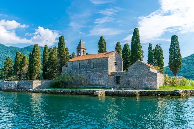 Jacht płynie w pobliżu malowniczej wyspy st. george w zatoce kotorskiej.