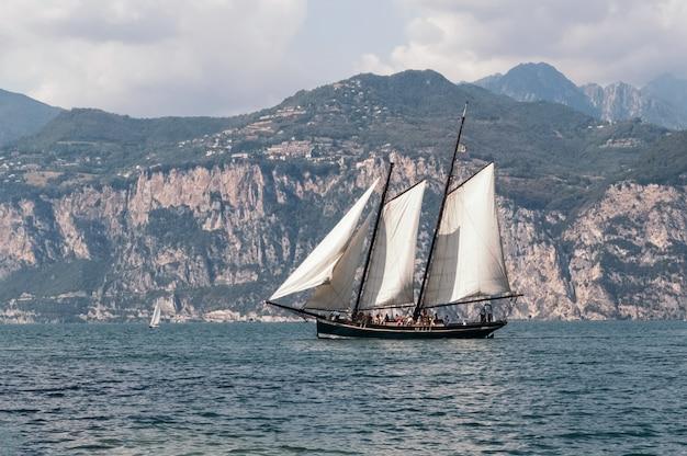 Jacht pływa na tle pasma górskiego