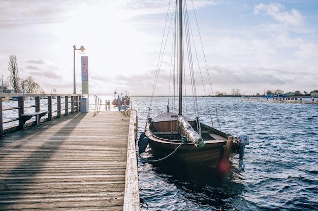 Jacht w pobliżu brzegu. niebieskie niebo i woda przy słonecznym dniem. pojęcie rekreacji i podróży.