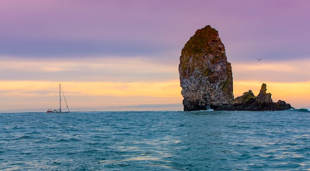 Jacht w pobliżu klifów z gniazdami mew na oceanie spokojnym