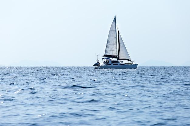Jacht z białymi żaglami na morzu