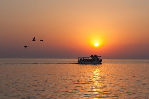 Jacht z turystami o zachodzie słońca z odlatującymi ptakami