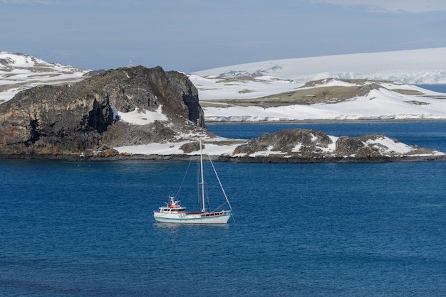 Jacht żaglowy i góra lodowa na morzu antarktycznym