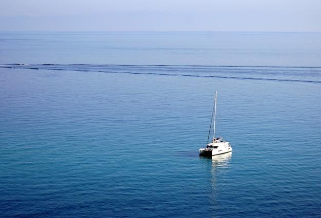 Jacht żaglowy na spokojnym oceanie w tropei