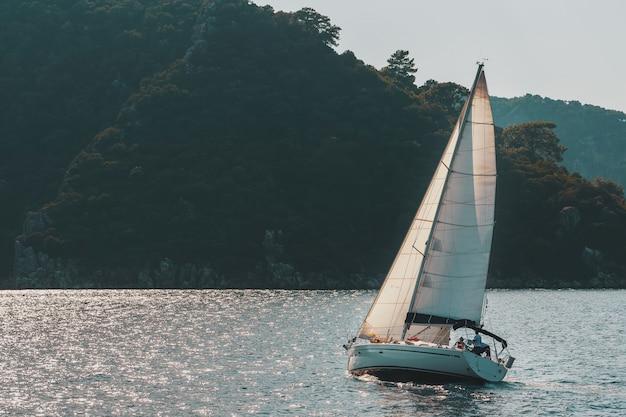 Jacht żaglowy z białymi żaglami na falistej zatoce morskiej w górach.