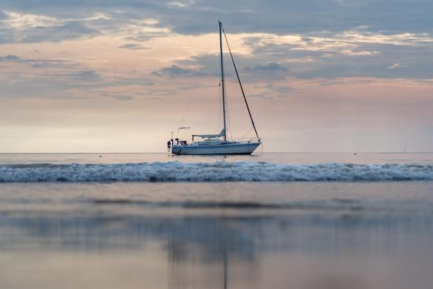 Jacht zaparkowany jest wieczorem przy plaży.