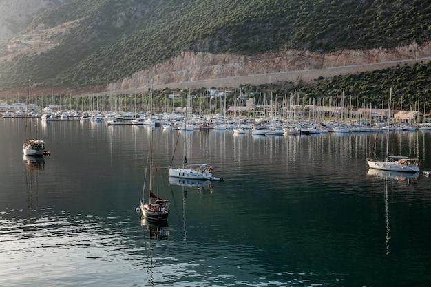 Jachty i małe drewniane łódki w pięknej marinie w małej miejscowości wypoczynkowej w górach. turystyka i podróże. jasny, słoneczny dzień.