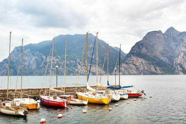 Jachty na brzegu jeziora garda iw alpach. włochy. toskania.