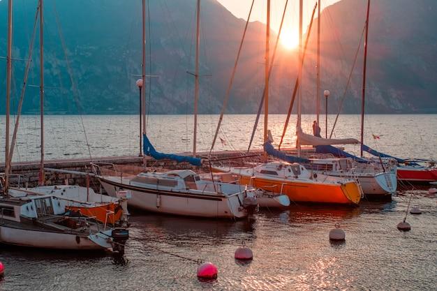 Jachty na molo podczas zachodu słońca nad jeziorem garda. zachód słońca nad riva del garda. słońce zachodzi w górach. jezioro na północy włoch.