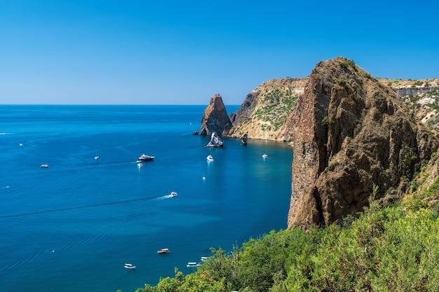 Jachty na morzu na tle skalistych brzegów. morze krajobraz z jachtami i skalistym wybrzeżem. skopiuj miejsce. koncepcja podróży, relaksu, aktywnego i zdrowego życia w zgodzie z naturą.