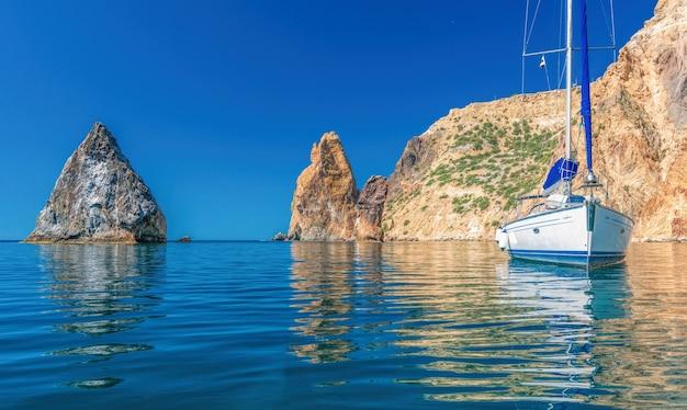 Jachty na morzu na tle skalistych brzegów. morze krajobraz z jachtami i skalistym wybrzeżem. skopiuj miejsce.