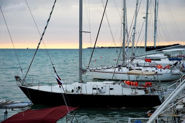 Jachty w pobliżu molo morskiego o zachodzie słońca