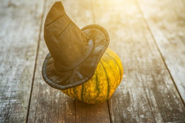 Jack o lantern halloween dynia z czarnym kapeluszem czarownicy na drewnianym tle. koncepcja strony halloween. świąteczne powitanie, upiorna sztuczka smakołyków.